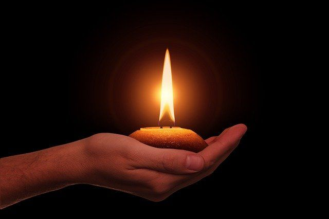 hand-holding-a-candle-in-dark-light