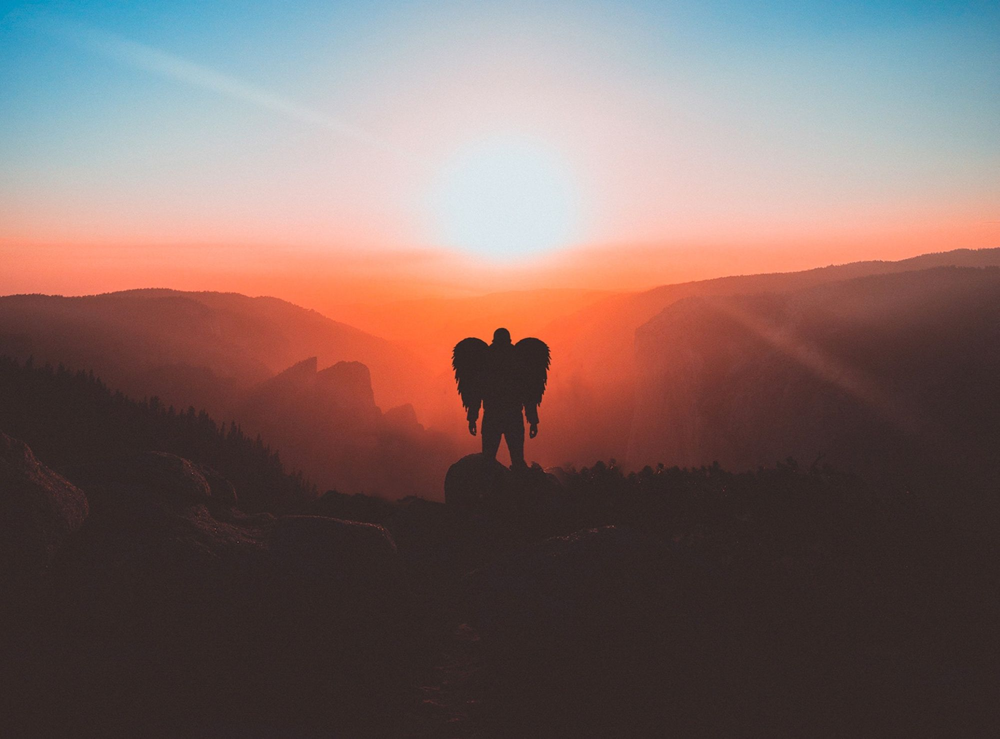man-with-wings-standing-on-brown-mountain-peak-2043837-2