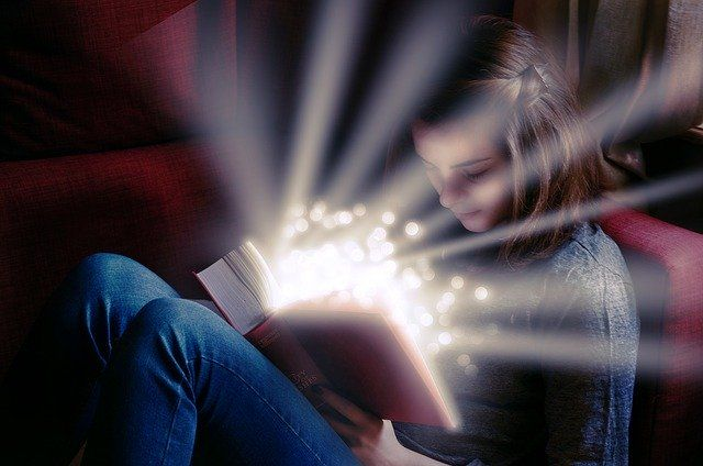 girl-sitting-on-couch-reading-a-red-book-emanating-rays-of-light-small