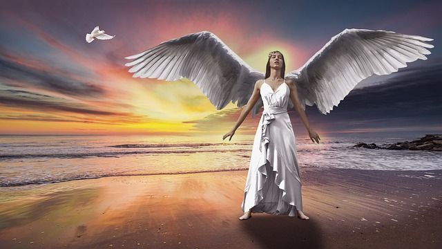 angel-woman-in-white-dress-spreading-wings-on-a-beach-with-sunset
