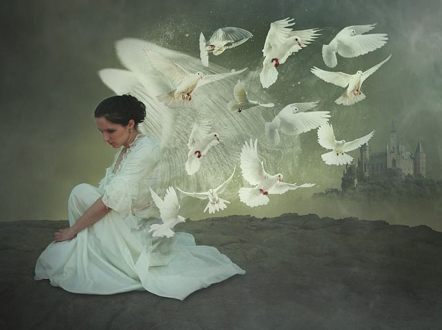winged woman in white dress sitting looking sad surrounded by white doves